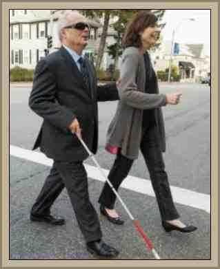 señora ayudando a un anciano ciego a  cruzar la calle